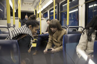 Female commuters texting with smart phone on bus - HEROF17999