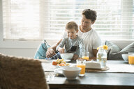 Father and son eating breakfast in breakfast nook - HEROF18050