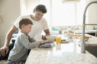 Father and son eating breakfast and using digital tablet at kitchen island - HEROF18056