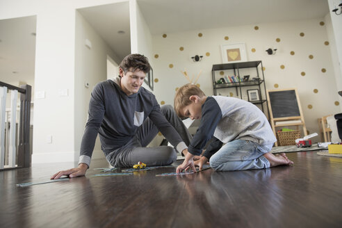 Father and son playing with track toy on floor - HEROF18062