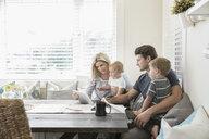 Family using digital tablet in breakfast nook - HEROF18068