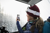 Female skier riding in gondola, photographing view with camera phone - HEROF18113