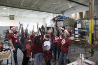 Community volunteers in Santa hats cheering in warehouse - HEROF18149