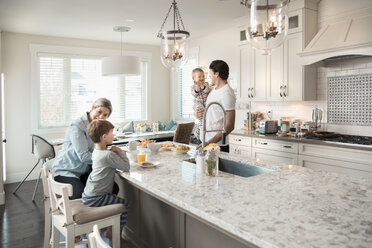 Family eating breakfast at kitchen island - HEROF18173