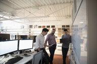 Designers brainstorming, meeting at whiteboard in creative office - HEROF18254