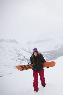 Confident female snowboarder carrying snowboard on snowy mountain - HEROF18278