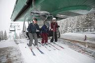 Family skiers getting off chair lift at ski resort - HEROF18296