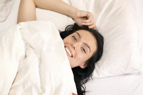 Beautiful woman lying in bed, smiling, portarit - PESF01198