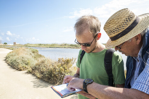 Italy, Sicily, Vendicari nature reserve, senior father and adult son looking at map - MAMF00377