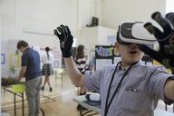 Boy middle school student using virtual reality simulator glasses at science fair - HEROF18330