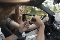 Boyfriend photographing girlfriend driving car, enjoying road trip - HEROF18390