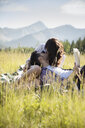 Affectionate young couple kissing and reading book in sunny summer rural field - HEROF18399