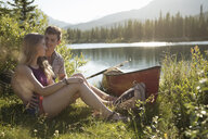 Affectionate, romantic young couple with canoe hugging at sunny summer lakeside - HEROF18402
