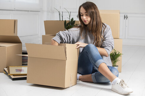 Woman sitting on the floor packing cardboard boxes - ERRF00731