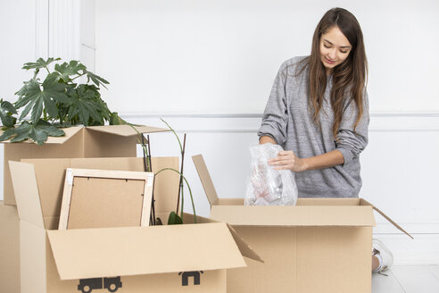 Woman packing cardboard boxes - ERRF00734