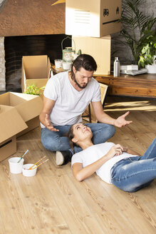 Couple with cardboard boxes in new home having a break - ERRF00740