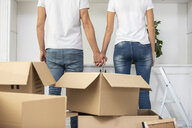 Close-up of couple with cardboard boxes standing hand in hand in new home - ERRF00746