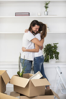 Couple with cardboard boxes hugging in new home - ERRF00749