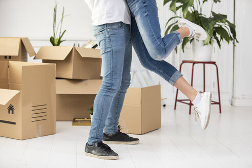Close-up of happy ouple with cardboard boxes hugging in new home - ERRF00752