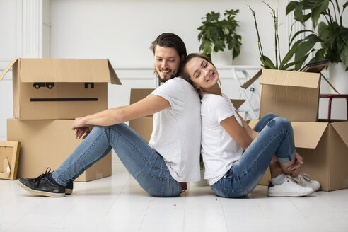 Happy couple with cardboard boxes sitting on the floor in new home - ERRF00755