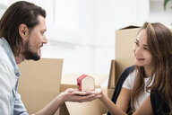 Man handing over tiny house model to girlfriend surrounded by cardboard boxes - ERRF00764