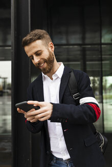 Smiling stylish businessman using cell phone in the city - JRFF02579
