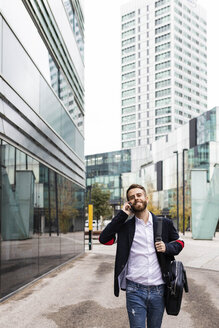 Spain, Barcelona. Portrait of young business man walking down the street and talking on the phone - JRFF02582