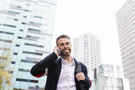 Stylish businessman talking on cell phone in the city - JRFF02585