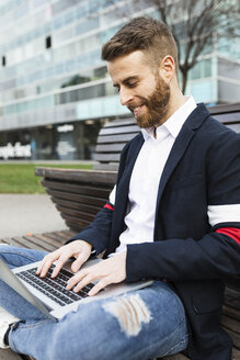 Stylish businessman sitting on bench in the city using laptop - JRFF02597