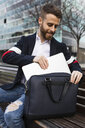 Stylish businessman sitting on bench in the city taking out laptop from bag - JRFF02600