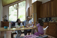 Father and daughters eating breakfast at kitchen table - HEROF18414