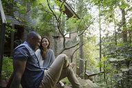 Couple talking on steps outside cabin in woods - HEROF18438