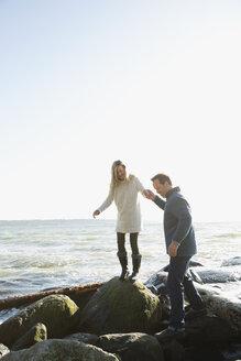 Couple holding hands walking on beach rocks - HEROF18459