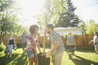 Couple carrying and planting tree in sunny backyard with friends - HEROF18525