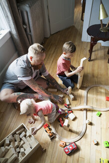 Father and children playing with wood blocks and toy train on floor - HEROF18543