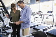 Couple looking at price tag on home gym cardio equipment in store - HEROF18585