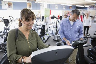 Couple browsing cardio machines at home gym equipment store - HEROF18588