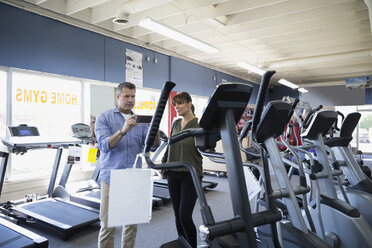 Couple with camera phone photographing elliptical machine at home gym equipment store - HEROF18591