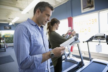 Couple reading treadmill information booklet in home gym equipment store - HEROF18594
