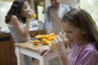 Girl drinking fresh squeezed orange juice in kitchen - HEROF18606