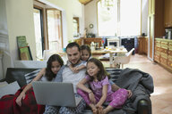 Father and daughters watching video on laptop on living room sofa - HEROF18609
