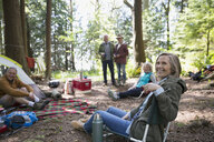Friends relaxing at campsite in woods - HEROF18627