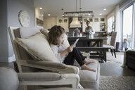 Girl using digital tablet on living room sofa - HEROF18666