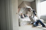 Father holding daughter overhead in bedroom - HEROF18672