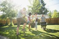 Friends planting tree in sunny backyard - HEROF18681
