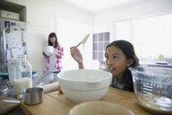 Girl examining batter baking in kitchen - HEROF18702
