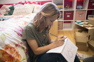Girl drawing designing jewelry in bedroom - HEROF18705