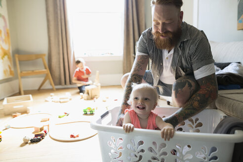 Father with happy daughter inside laundry basket - HEROF18738