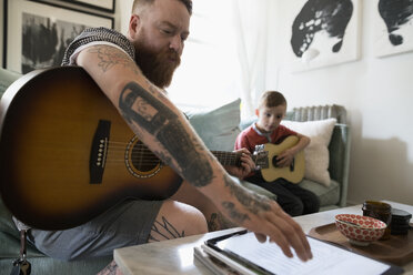 Father with digital tablet teaching son playing guitar in living room - HEROF18747