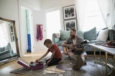 Father and son with guitar playing records on living room floor - HEROF18750